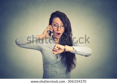 Business and time management concept. Stressed businesswoman looking at wrist watch, running late for meeting