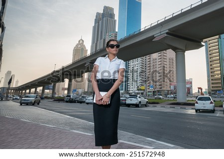 Business and woman. Successful arabic businesswoman standing in the street in formal attire. Businessman standing near skyscrapers in Dubai downtown in sunglasses holding a tablet