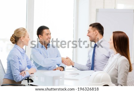 business, architecture and office concept - happy team of architects and designers in office shaking hands - stock photo
