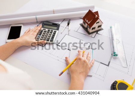 business, architecture, building, construction and people concept - close up of architect hand with blueprint counting on calculator - stock photo