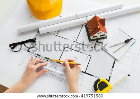 business, architecture, building, construction and people concept - close up of architect hands with ruler and pencil measuring living house blueprint - stock photo