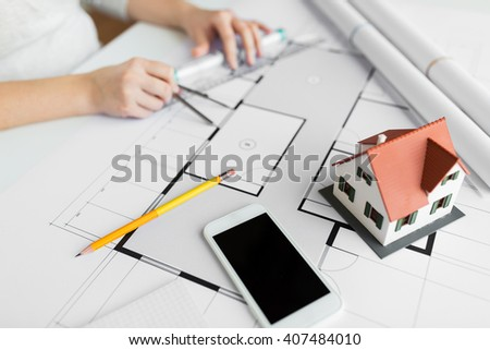 business, architecture, building, construction and people concept - close up of smartphone and living house layout over architect hands with compass measuring blueprint - stock photo