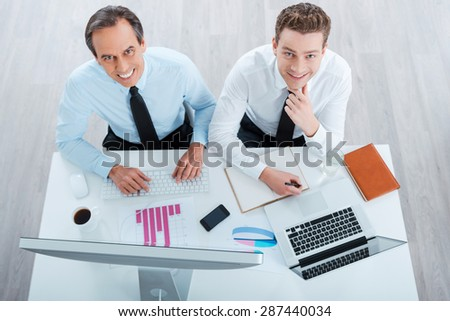 Business as usual. Top view of two cheerful business people in formalwear working and looking at camera while sitting at working place - stock photo