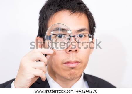Business asian man Looking At camera Through Magnifying Glass close up on white