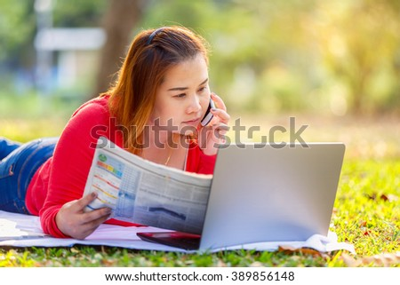Business asian woman reading newspaper and working with laptop on the grass in park and talking on a phone - stock photo