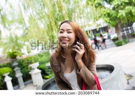 Business asian woman using mobile smart phone at outdoors. - stock photo