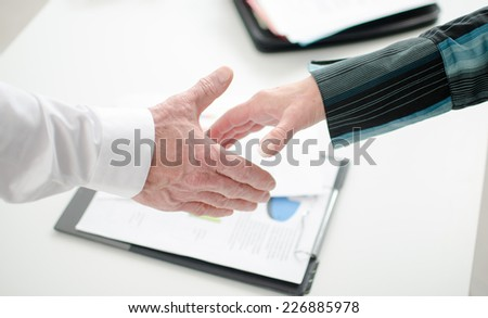 Business associates getting ready to shake hands in office - stock photo