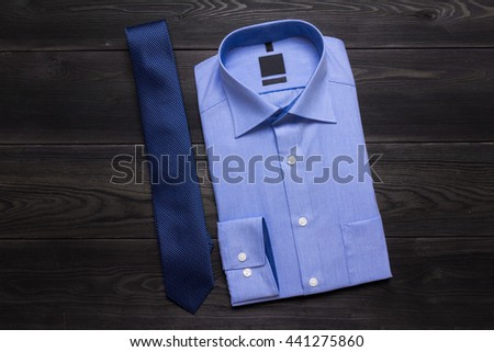 Business background. Blue formal shirt and blue necktie on black wooden table. Copy space - stock photo