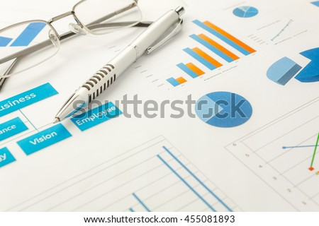 business background grown up concept the pen and eyeglasses  on business chart document background.