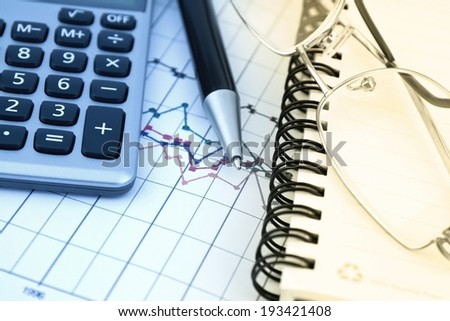 Business background with charts, pen and calculator in blue and yellow - stock photo