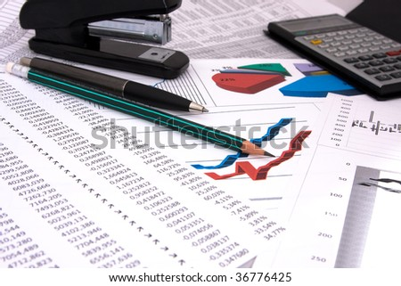 Business background with financial report, pen and pencil, calculator and stapler - stock photo