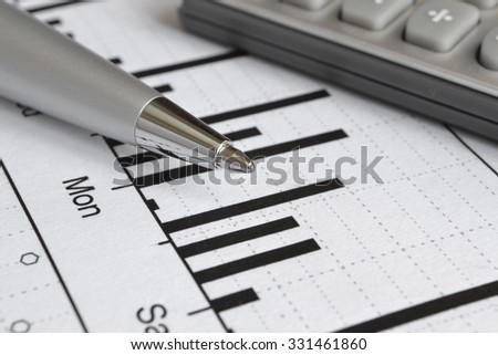 Business background with graph, pen and calculator.