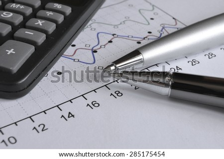 Business background with graph, pens and calculator. - stock photo