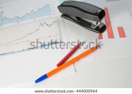 Business background with pen, pencil and stapler - stock photo