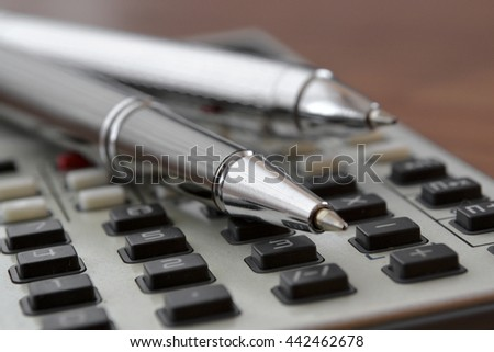 Business background with table, pens and calculator. - stock photo