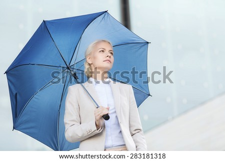 business, bad weather and people and concept - young serious businesswoman with umbrella outdoors - stock photo