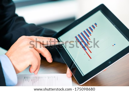 Business - banker, Manager or expert evaluates the figures on tablet computer and compares the development of the business in real time to quickly and efficient advise and act as consultant - stock photo