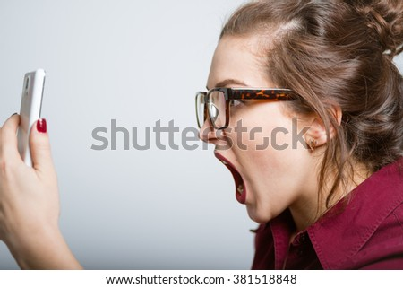 Business beautiful shouting on the phone, isolated on gray background - stock photo
