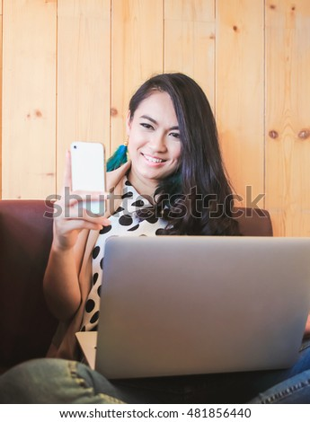 Business beautiful woman using smartphone and laptop on couch at home or cafe