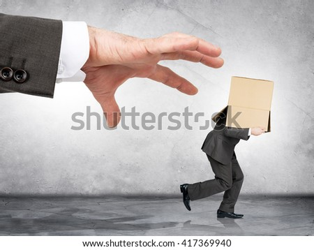 Business boss hand catching employee with box on his head - stock photo