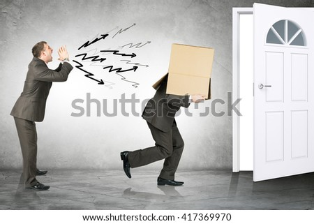 Business boss shouting to employee with box on his head and running away - stock photo