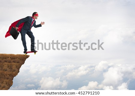 business bravery courage concept superhero businessman leaping off a cliff on a skateboard - stock photo