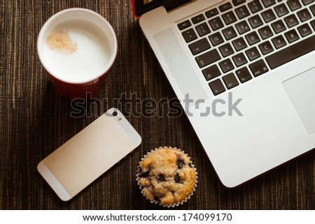 business breakfast with cafe, muffin, laptop and cellphone - stock photo