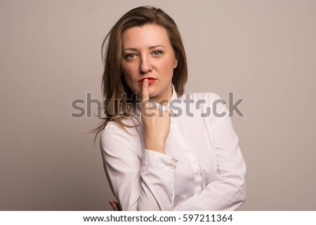 Business brunette in a white shirt covers her finger with her lips, quietly