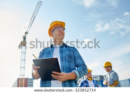 business, building, paperwork and people concept - happy builder in hardhat with clipboard and pencil over group of builders at construction site - stock photo