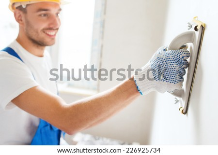 business, building, profession and people concept - smiling builder with grinding tool indoors - stock photo