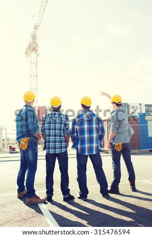 business, building, teamwork and people concept - group of builders in hardhats outdoors from back - stock photo