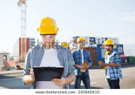 business, building, teamwork and people concept - group of builders in hardhats with clipboard outdoors - stock photo