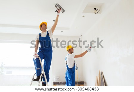business, building, teamwork and people concept - group of builders in hardhats with plastering tools indoors - stock photo