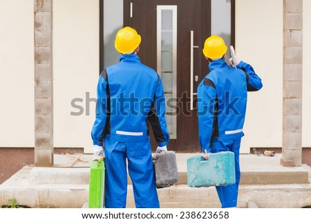 business, building, teamwork and people concept - group of builders in hardhats with toolboxes outdoors from back - stock photo