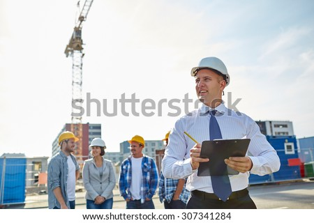 business, building, teamwork and people concept - group of smiling builders and architect with clipboard in hardhats at construction site - stock photo