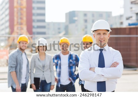 business, building, teamwork and people concept - group of smiling builders in hardhats outdoors
