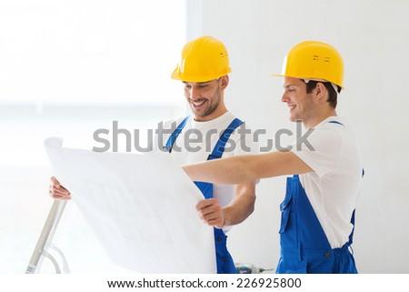 business, building, teamwork and people concept - group of smiling builders in hardhats with blueprint indoors - stock photo