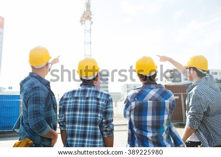 business, building, teamwork, development and people concept - group of builders in hardhats at construction site pointing finger to crane from back