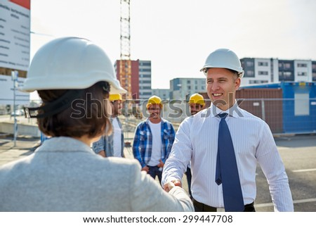 business, building, teamwork, gesture and people concept - group of smiling builders or architects in hardhats greeting each other by handshake on construction site - stock photo