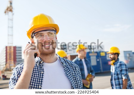 business, building, teamwork, technology and people concept - group of smiling builders in hardhats with radio outdoors