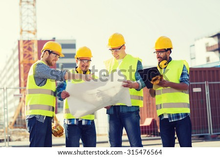 business, building, teamwork, technology and people concept - group of smiling builders in hardhats with tablet pc computer and blueprint outdoors