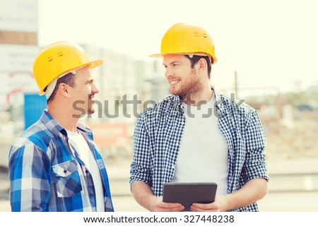 business, building, teamwork, technology and people concept - group of smiling builders in hardhats with tablet pc computer outdoors