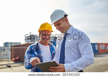 business, building, teamwork, technology and people concept - smiling builders in hardhats with tablet pc computer at construction - stock photo