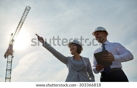 business, building, teamwork, technology and people concept - smiling man and woman in hardhats with tablet pc computer pointing finger up at construction site