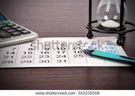 business calendar page on table, sandglass, calculator and pen, close up