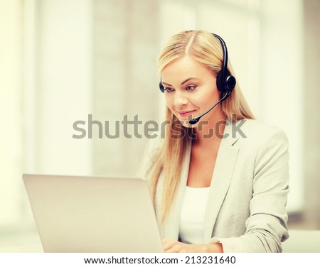 business, call centre and technology concept - female helpline operator with headphones and laptop pc - stock photo
