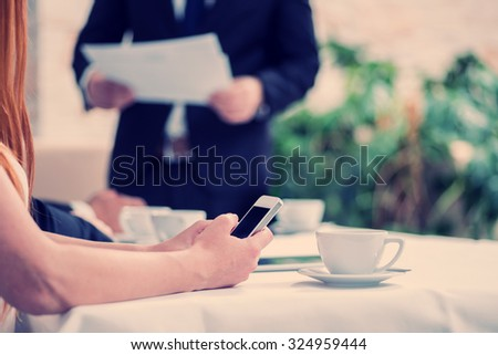 Business call client. Four smiling successful businessmen sitting at table in office while discussing their of business doings. Young people talking in office - stock photo
