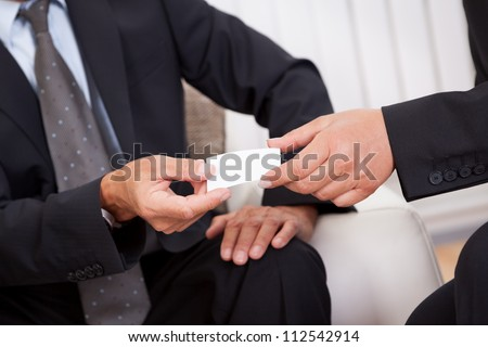 Business card being passed over between a male and female businessperson in suits - stock photo