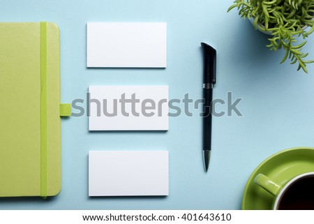 Business card blank, notepad, flower, coffee cup and pen at office desk table top view. Corporate stationery branding mock-up - stock photo