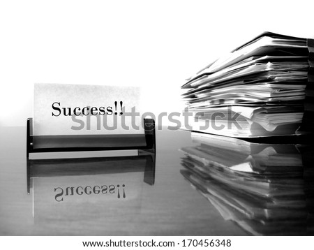 Business card on desk with files and word Success